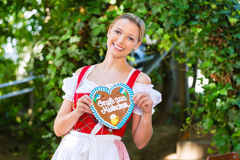 Woman with gingerbread hart in Bavaria beergarden. Young woman in traditional Bavarian clothes or tracht with a gingerbread souvenir heart in beergarden on Royalty Free Stock Photography