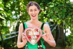 Woman with gingerbread hart in Bavaria beergarden. Young woman in traditional Bavarian clothes or tracht with a gingerbread souvenir heart in beergarden on Royalty Free Stock Photo