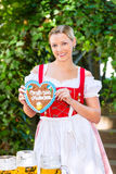 Woman with gingerbread hart in Bavaria beergarden. Young woman in traditional Bavarian clothes or tracht with a gingerbread souvenir heart in beergarden on Royalty Free Stock Images