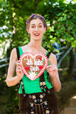 Woman with gingerbread hart in Bavaria beergarden Royalty Free Stock Photos