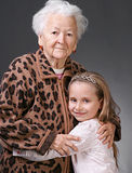 Woman and girl. Closeup portrait of senior women with little granddaughter on a gray background background royalty free stock images