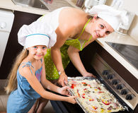 Woman and girl baking pizza at home Stock Photo