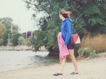 Woman girl on beach on windy cold day. Portrait of woman girl walking on beach with lunchbox and blanket on cold windy summer autumn day with her face away from Stock Photography