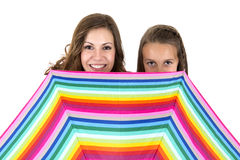 Woman and a girl behind a rainbow colored umbrella Stock Photography