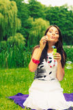 Woman girl blowing soap bubbles outdoor. Royalty Free Stock Images