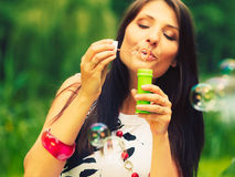 Woman girl blowing soap bubbles outdoor. Royalty Free Stock Photography