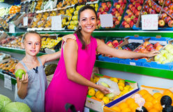 Woman with girl buying apples Stock Photos