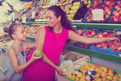 Woman with girl buying apples Royalty Free Stock Photography