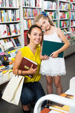 Woman with girl buying books Stock Image
