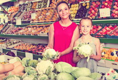 Woman with girl buying cabbage Stock Photo