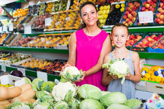 Woman with girl buying cabbage Royalty Free Stock Photos