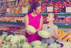 Woman with girl buying cabbage Stock Photography