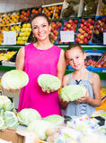 Woman with girl buying cabbage Royalty Free Stock Image