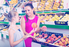 Woman with girl buying peaches Stock Photography