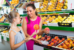Woman with girl buying peaches Stock Photos