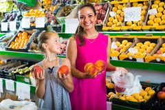 Woman with girl buying peaches Stock Photo
