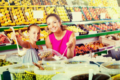 Woman with girl buying pickled olives Royalty Free Stock Photos