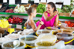 Woman with girl buying pickled olives Royalty Free Stock Photo