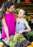 Woman with girl buying ripe grapes Stock Photos