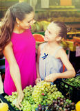 Woman with girl buying ripe grapes Stock Images