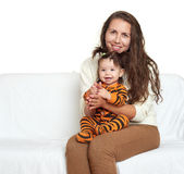 Woman with girl child portrait sitting on sofa and playing Royalty Free Stock Image