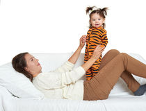 Woman with girl child portrait sitting on sofa and playing Stock Images