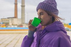 Pretty young girl drinks coffee or tea, street Stock Image