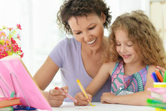 Woman and  girl with colored pencils Stock Photos