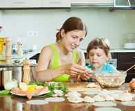 Woman with a girl cooking red fish dumplings together at home ki Royalty Free Stock Photography
