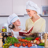 Woman and girl cooking veggies Royalty Free Stock Photos