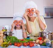 Woman and girl cooking veggies Stock Photo