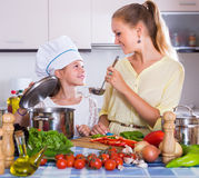 Woman and girl cooking veggies Stock Photography