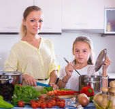 Woman and girl cooking veggies Royalty Free Stock Image