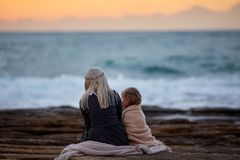 Woman with girl cuddling on seashore royalty free stock image
