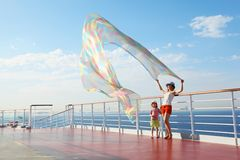 Woman and girl on deck of ship. Woman with kerchief standing on deck of cruise ship. her daughter looking at kerchief Stock Photo