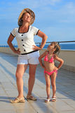 Woman and girl do morning exercise on veranda Stock Photo