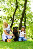 Woman, girl and dog on the grass. Stock Photography