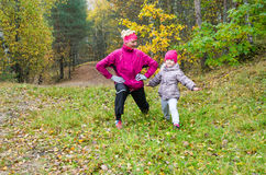 Woman with girl doing aerobics in autumn park Royalty Free Stock Photo