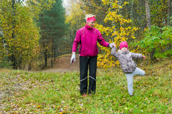 Woman with girl doing aerobics in autumn park Stock Image