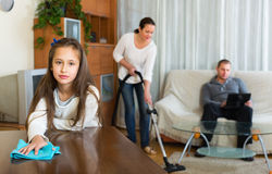 Woman and girl doing cleaning. Woman and girl doing general cleaning, men having rest Royalty Free Stock Image