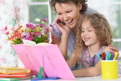 Woman and girl doing homework. Smiling women and a little girl doing homework together Stock Image