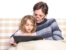 Woman and girl doing homework on tablet pc Stock Photo
