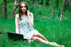 Woman or girl in a dress, with a laptop and headphones, sits on Royalty Free Stock Image