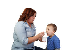 Woman girl feeds little boy Stock Image