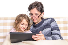 Woman and girl having fun on tablet pc Royalty Free Stock Photos