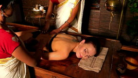 Woman girl having spa treatment. Two real Indian masseuses massage hands.