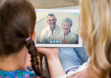 Woman and girl having a video call with senior couple on digital tablet Stock Image