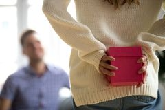 Woman hiding present making surprise for happy husband, rear view