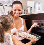 Woman and girl holding baking tray stock photo