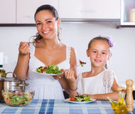 Woman and girl holding salad Stock Photos